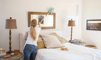 Woman cleaning bedroom.