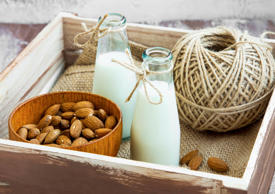 Almond milk in bottles with almond nuts bowl in wooden box
