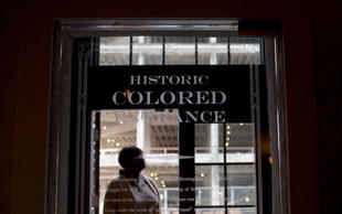 "In this Thursday, Jan. 7, 2016 photo, a woman stands in the doorway of then new Historic Colored Entrance at the Lyric Theatre, in Birmingham, Ala. Preservationists had to decide whether to keep reminders of The Lyric's discarded color line before they unveiled an $11 million restoration of the 102-year-old theater, which had been closed for decades. In this case, they chose to highlight the history, installing a glass door with the etched words ""Historic Colored Entrance"" in the lobby wall so patrons can peer into the past. (AP Photo/Brynn Anderson)"