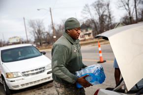 FLINT, MI - FEBRUARY 7: Army National Guard Spc. Terence Burse carries bottled water out to the car for a resident on February 7, 2016 in Flint, Michigan. Months ago the city told citizens they could use tap water if they boiled it first, but now say it must be filtered to remove lead.