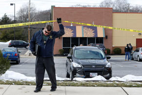An investigator walks beneath a police tape line at the scene of a shooting at a shopping center in Abingdon, Md., Wednesday, Feb. 10, 2016. A man opened fire inside a shopping center restaurant during lunchtime.