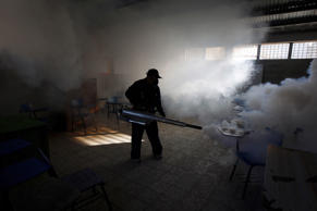 A municipal health worker fumigates a classroom as part of the city's efforts to...