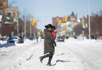 A woman holds a child as she navigates through the snow February 2, 2015 in Detroit, Michigan.