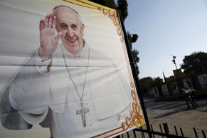 People walk past a banner with a picture of Pope Francis near the Basilica of Gu...