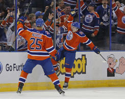 Feb 11, 2016; Edmonton, Alberta, CAN; Edmonton Oilers forward Connor McDavid (97) celebrates his first period goal against the Toronto Maple Leafs with defensemen Darnell Nurse (25) at Rexall Place.
