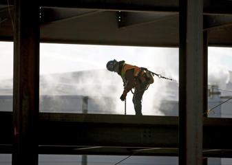 A worker braves cold temperatures while working atop steel beams at the Albany convention center project on Friday, Feb. 12, 2016, in Albany, N.Y. The National Weather Service has issued lake-effect snow warnings that remain in effect until late Friday night for western New York and into early Saturday for northern New York, while wind chill warnings are in effect for most of the upstate region through the weekend.
