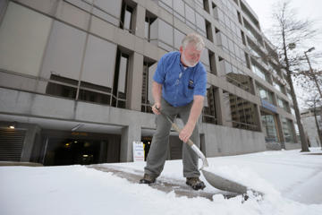 A man who wished not to be identified shovels snow and ice in downtown Little Rock, Ark., Monday, Feb. 16, 2015.