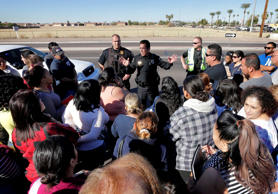 A Glendale police officer tries to give instructions to parents waiting to reuni...