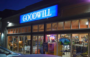 A Goodwill retail store front in the Capitol Hill neighborhood of Seattle, Washington. Cars are parked outside and thrift goods are seen through the windows of this urban location.