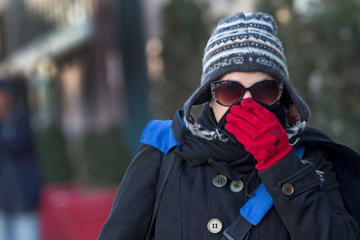 A woman lifts her scarf up in front of her nose to shield from the cold air, Friday, Feb. 12, 2016, in New York. The National Weather Service predicts temperatures well below freezing on Saturday for New York. But wind chills could drop even lower, and wind gusts could reach around 44 mph.