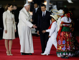 Pope Francis reaches out to greet youth dressed in traditional Mexican outfits as he's escorted by Mexico's President Enrique Pena Nieto, behind, and first lady Angelica Rivera, upon arrival to Benito Juarez International Airport in Mexico City, Friday, Feb. 12, 2016. The pontiff is in Mexico for a week-long visit.