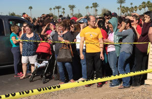 Parents and others wait near a high school in Glendale, Ariz., to be reunited with students after police say two female students died in a shooting at the school in a Phoenix suburb.