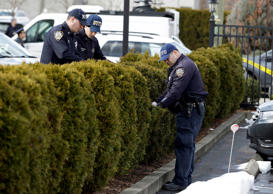 Police officers search bushes in the parking lot of a Ramada Inn where authorities say a man stabbed a woman and her children in the Staten Island borough of New York, Wednesday, Feb. 10, 2016.