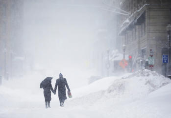 A couple walks hand-in-hand through the snow in Exeter Street in the Back Bay during a winter blizzard in Boston, Massachusetts, United States February 15, 2015.