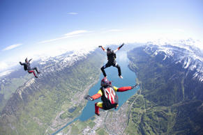 Team of three skydivers in formation over Interlaken, Berne, Switzerland