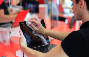 An employee cleans the screen of a Lenovo Group Ltd. Yoga 2 11 laptop computer at the company's trade stand at the IFA Consumer Electronics Show in Berlin, Germany, on Friday, Sept. 5, 2014.