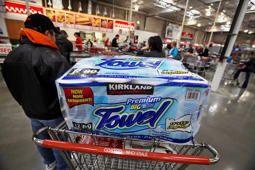 A shopper stands in line with his purchases including Costco's Kirkland Signature brand paper towels inside a Costco store in Mount Prospect, Illinois, U.S.