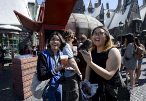 "Guests try out Butterbeer served from a large barrel shaped Butterbeer cart in Hogsmeade Village during a soft opening and media tour of ""The Wizarding World of Harry Potter"" theme park at the Universal Studios Hollywood in Los Angeles"