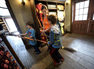 "A mother and her children try out witch brooms for sale during a soft opening and media tour of ""The Wizarding World of Harry Potter"" theme park at the Universal Studio:"