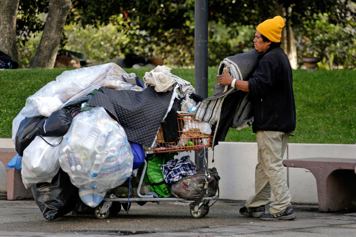 A homeless man packs up his blankets in downtown Los Angeles, Friday, Nov. 27, 2015.