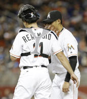 Miami Marlins catcher J.T. Realmuto (11) talks to Wei-Yin Chen (54) after Chen g...