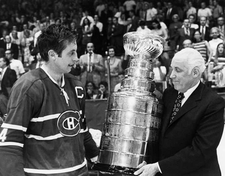 FILE - In this May 18, 1971, file photo, Montreal Canadiens' captain Jean Beliveau, left, is presented the Stanley Cup by NHL Commissioner Clarence Campbell after Montreal beat Chicago in Game 7 of the Stanley Cup finals.
