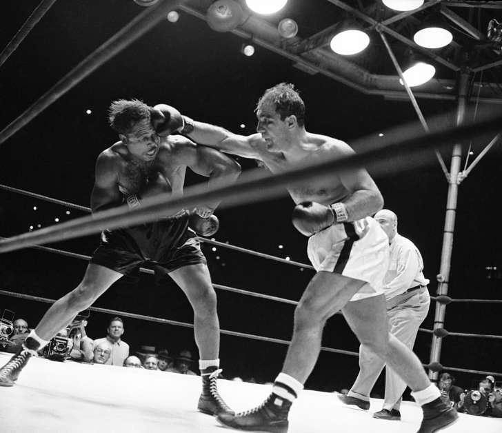 Heavyweight champion Rocky Marciano's right fist made challenger Archie Moore's hair stand on end-like this-more than once during their title bout at Yankee Stadium in New York City, Sept. 21, 1955. Marciano retained his crown when he dropped Moore by a knockout in the ninth round of their scheduled 15-round bout. Note how Moore's gloves are well away from punch in this action.