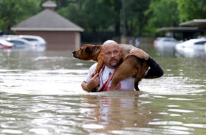 Louis Marquez carries his dog Dallas through floodwaters after rescuing the dog ...