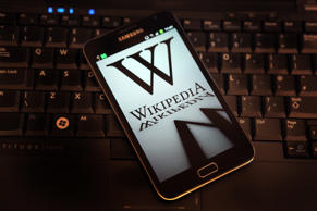 File: A mobile device shows Wikipedia's front page displaying a darkened logo on January 18, 2012 in London, England.