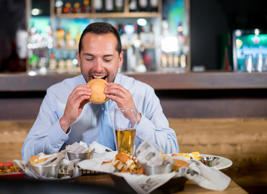 Man eating burger at bar.