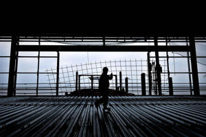 A construction worker is silhouetted as he carries steel mesh past the end of the pier