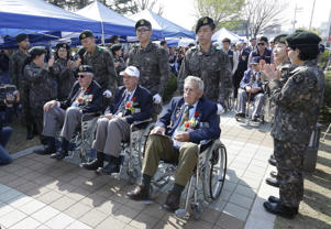 Commonwealth nations forces veterans in wheel chairs are greeted by South Korean army reserve women as they arrive to attend a ceremony to commemorate the 64th anniversary of a fierce Korean War battle, in which Commonwealth nations forces fought off Chinese troops at Gapyeong, South Korea, Friday, April 24, 2015.