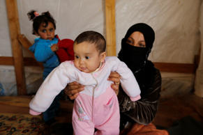 Syrian refugee Asheqa holds her unregistered baby daughter Nour inside a tent at a refugee camp near the town of Baalbek in LebanonÕs Bekaa valley, March 3, 2016.