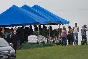 Mourners gather around caskets at Scioto Burial Park during funeral services for six of the eight murder victims from Pike County, Tuesday, May 3, 2016, in McDermott, Ohio. Seven adults and a 16-year-old boy from the Rhoden family were found dead April 22 at four properties scattered across a few miles of countryside near Piketon, about 80 miles east of Cincinnati. . (AP Photo/John Minchillo)
