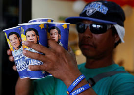 "A mall parking attendant and supporter of presidential candidate Rodrigo Duterte for the May 9 election, holds ""Big Gulp"" soda cups he bought from convenience store 7-Eleven, in Paranaque, Metro Manila, Philippines April 25, 2016."