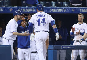 Justin Smoak #14 of the Toronto Blue Jays is congratulated by Marcus Stroman #6 after hitting a game-tying solo home run in the ninth inning during MLB game action against the Texas Rangers.