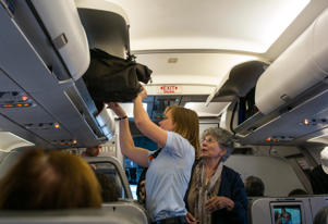 A passenger gets help with her carry-on luggage from a flight attendant.