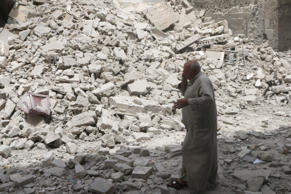 A man walks past the rubble of damaged buildings after an airstrike in the rebel held area of Aleppo's Baedeen district