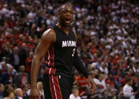 Dwayne Wade of the Miami Heat celebrates after making a play against the Toronto...
