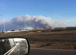 Vehicles are seen on highway 63 as they are detoured near wildfire burning near ...