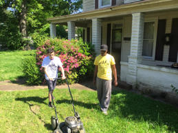 Raising Men Lawn Care Service employees mow a lawn in Alabama