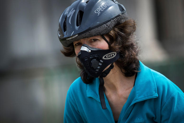 File photo: A woman wearing an anti-pollution mask rides a bicycle at Hyde Park Corner.