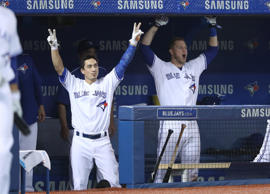 Darwin Barney #18 and Michael Saunders #21 celebrate in the dugout after Russell Martin #55 of the Toronto Blue Jays hits a game-winning RBI single in the ninth inning during MLB game action against the Texas Rangers on May 4, 2016 at Rogers Centre in Toronto.