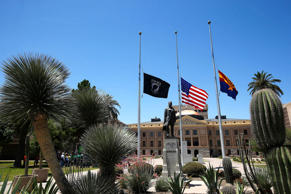 Flags fly at half-staff in remembrance of Arizona native U.S. Navy Petty Officer 1st Class Charles Keating IV, at the Arizona Capitol Wednesday, May 4, 2016, in Phoenix. The Navy SEAL was shot and killed Tuesday in Iraq during a gunbattle involving Islamic State fighters.