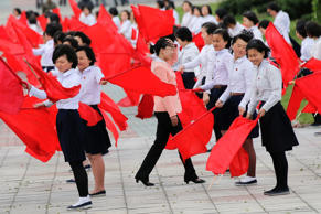 Strong wind blows as girls practice dancing with red flags in central Pyongyang, North Korea May 4, 2016.
