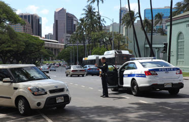 A Honolulu police officer directs traffic on a downtown street