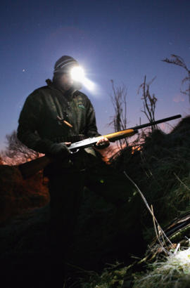 A duck hunter prepares his weapon.