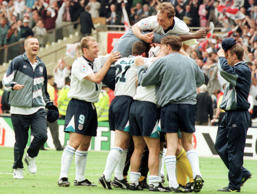 David Platt, centre, jumps on top a pile of England players as they mob goalkeeper David Seaman following their 4-2 victory over Spain in a penalty shootout in a European Soccer Championships quarter-final match at London's Wembley Stadium Saturday June 22, 1996. (AP Photo/Santiago Lyon)