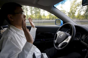 Li Zengwen, a development engineer at Changan Automobile, lifts his hands off the steering wheel as the car is on self-driving mode during a test drive on a highway in Beijing, China, April 16, 2016.