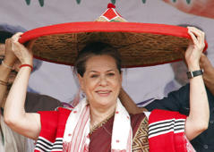 "File: Sonia Gandhi, Chief of the ruling Congress party, wears a ""Japi"" (a traditional hat of Assam) presented to her by party members during a rally ahead of the general election in Lakhimpur in the northeastern Indian state of Assam March 30, 2014."